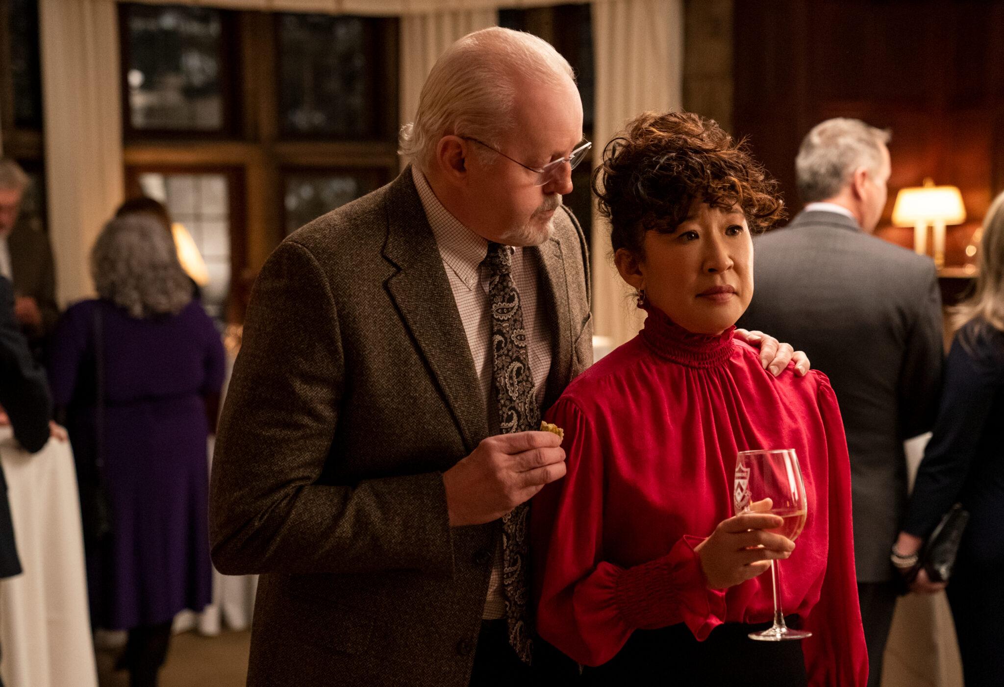 David Morse steht hinter Sandra Oh und legt ihr seine linke Hand auf die Schulter. Sie trägt ein rotes Kleid und in der rechten Hand ein Weinglas, halb gefüllt. Hinter den beiden sieht man einige Personen auf der Abendgesellschaft.