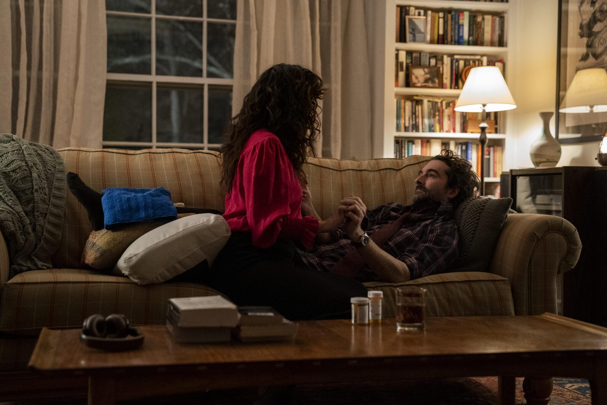 In einem Wohnzimmer sitzt Sandra Oh auf der Couch vor einem Bücherregal während neben ihr Jay Duplass liegt. Beide halten sich an der Hand. Im Vordergrund sieht man einen Couchtisch auf dem einige Bücher, ein Kopfhörer, ein Glas und zwei Dosen mit Pillen stehen.
