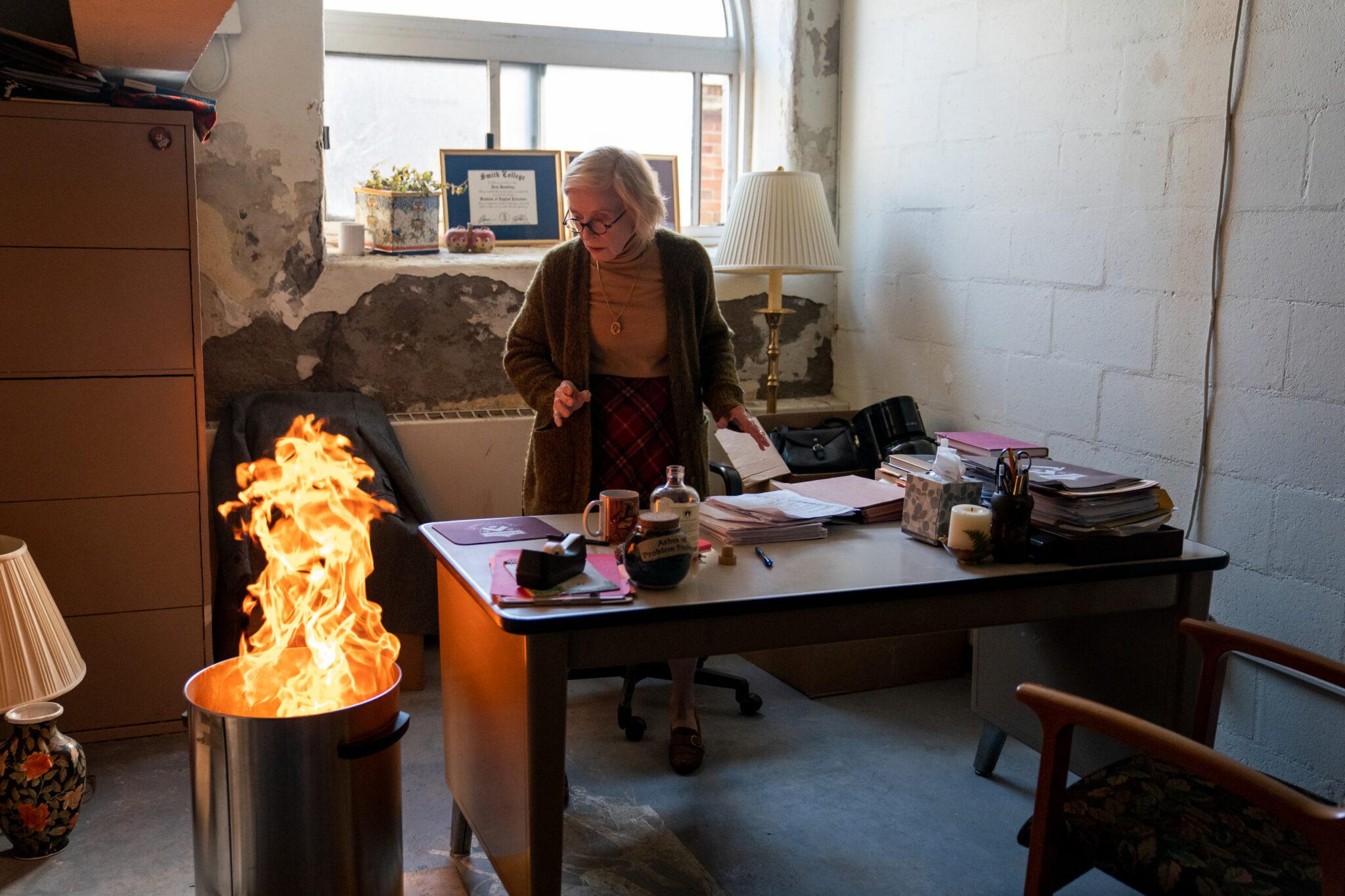 Joan (Holland Taylor) steht hinter ihrem Schreibtisch. Neben diesem steht eine Metalltonne aus der Feuer herausbricht.