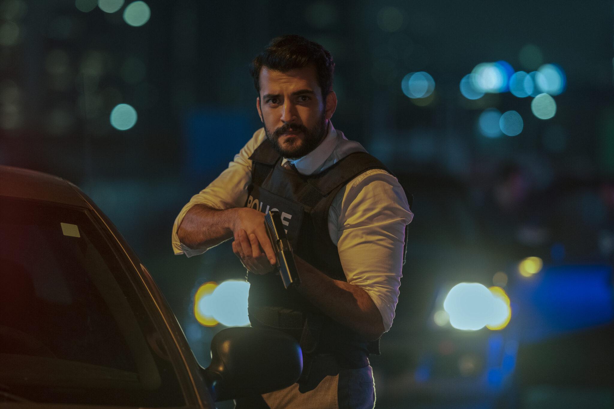 Phoenix Raei als Polizist in Clickbait. Er steht im Dunkeln neben einem Auto mit Schussweste und Pistole im Anschlag.
