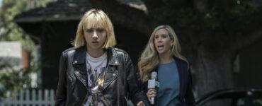 Pia Brewer (Zoe Kazan) läuft in Clickbait sichtlich erschüttert eine Straße entlang, während sie von einer fragenden Reporterin verfolgt wird.