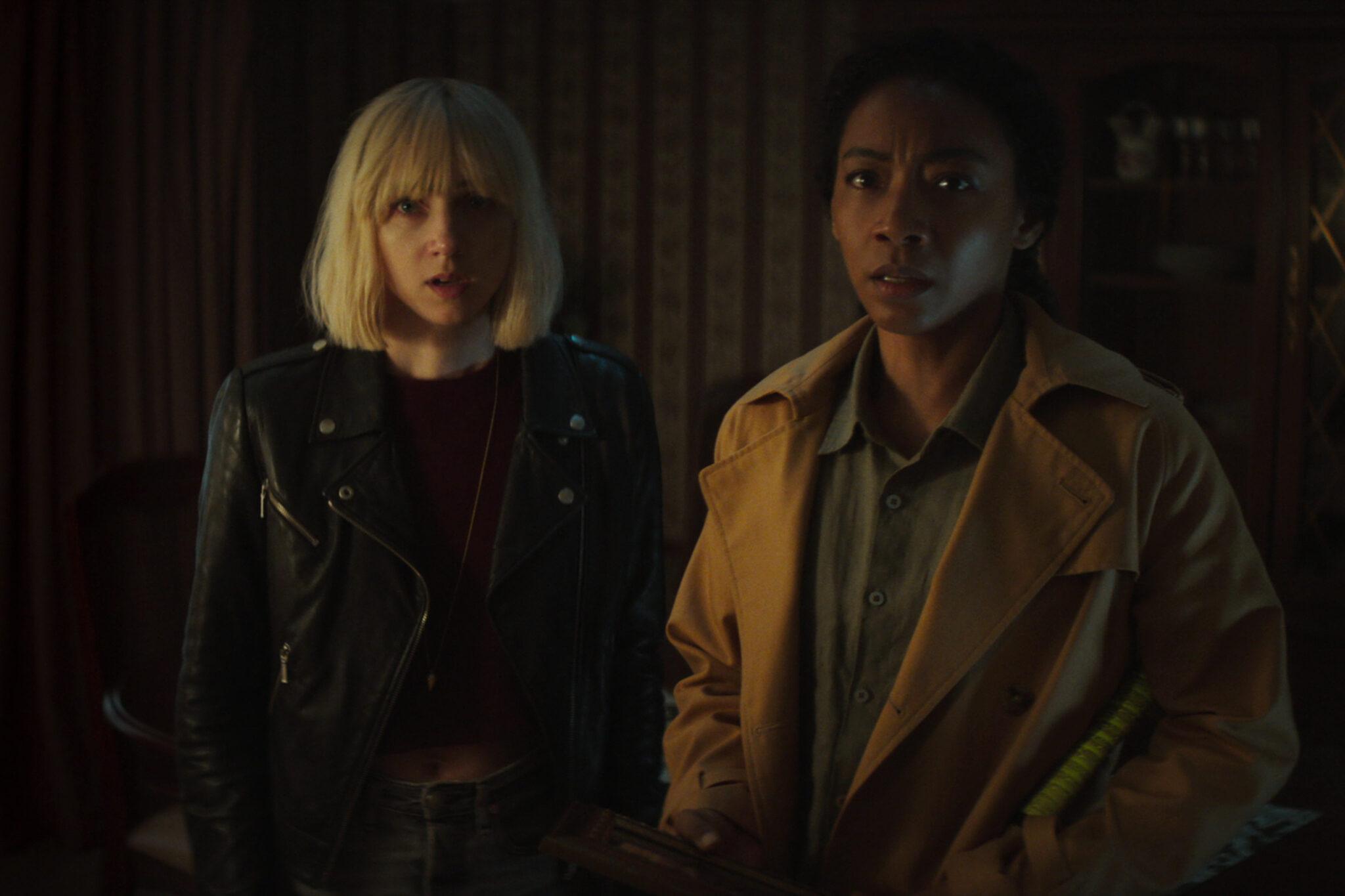 Zoe Kazan steht in Clickbait in einem dunklen Raum leicht versetzt links hinter Betty Gabriel. Beide wirken leicht verblüfft und schauen in Richtung Kamera.