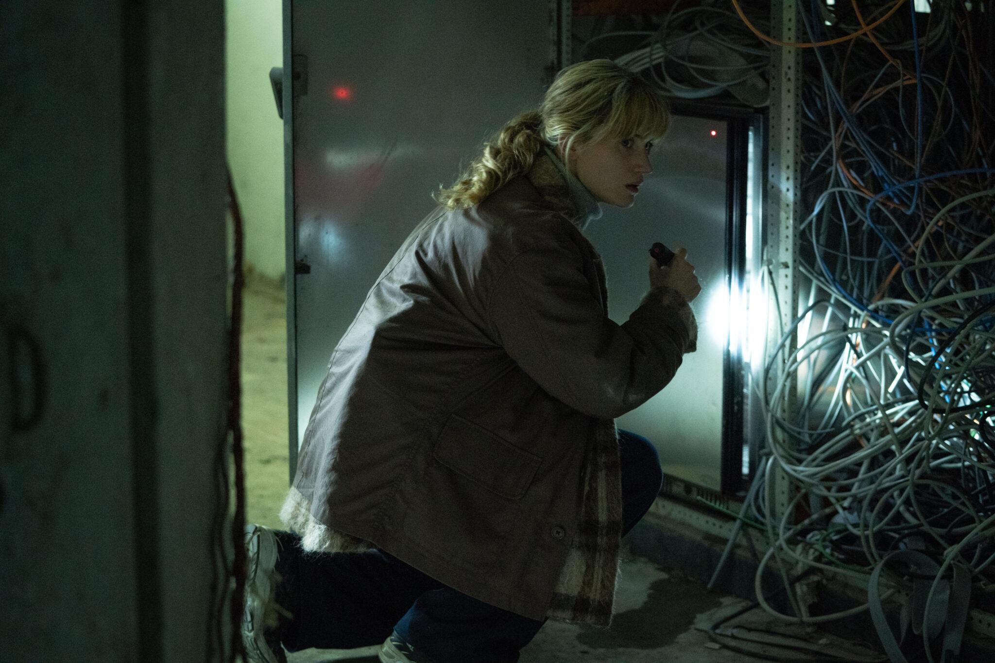 Die Ermittlerin mit Taschenlampe vor einem Stromkasten kniend, aus dem unzählige Kabel herausschauen.