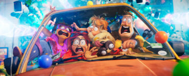 Die Familie Mitchell mit erschrockenen Gesichtern zusammengedrängt in ihrem orangen Auto. Im Hintergrund fliegen die verfolgenden Roboter heran.