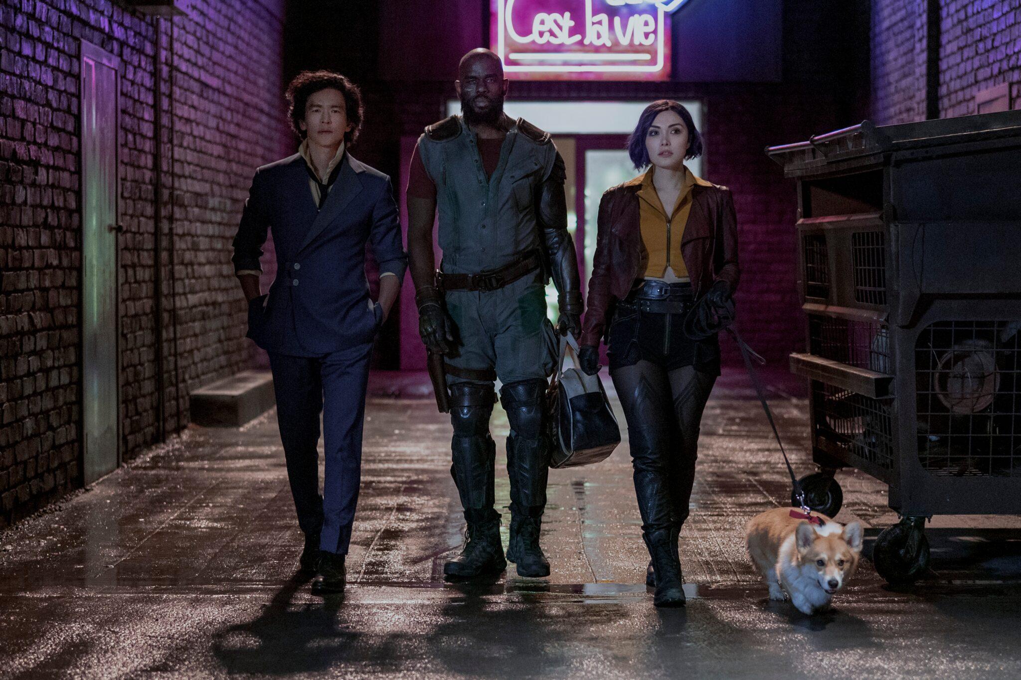 John Cho, Mustafa Shakir und Daniella Pineda laufen in einer nächtlich dunklen Gasse mit einem kleinen Hund.