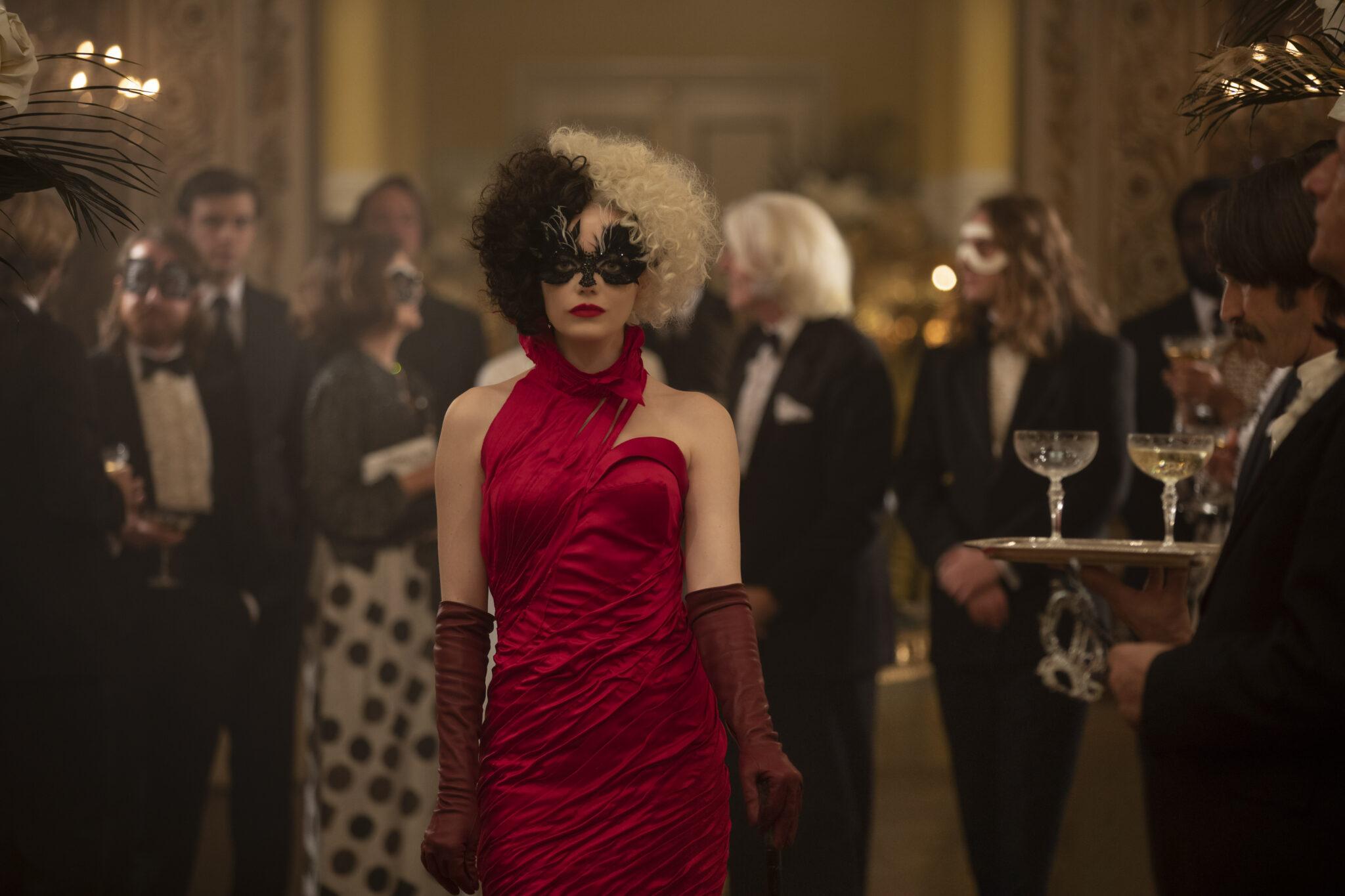 Emma Stone als Cruella in einem knallroten Abendkleid mit schwarzweißen Haaren und einer schwarzen Maske. Hinter ihr sieht man einige edel gekleidete Mitglieder der Abendgesellschaft.