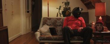 Matthew C. Vaughan sitzt als Ted in Cat Sick Blues mit Katzenmaske auf dem Kopf auf einem Sofa