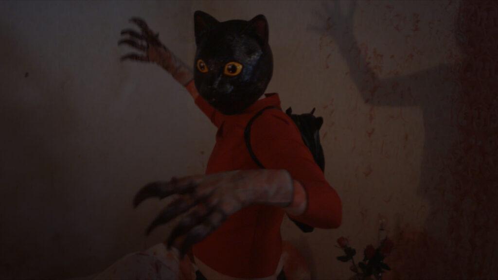 Matthew C. Vaughan als Ted in Cat Sick Blues mit einer Katzenmaske auf dem Kopf und krallenbestückten Handschuhen holt mit der rechten Hand zum Schlag aus.