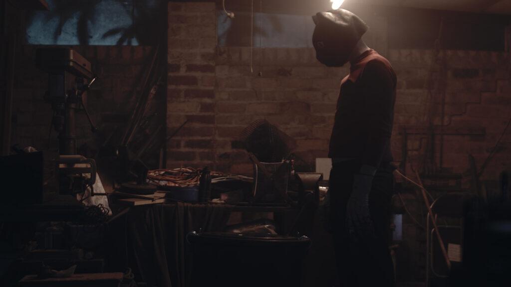 Matthew C. Vaughan steht als Ted in Cat Sick Blues mit Katzenmaske auf dem Kopf in einem zugerümpelten Keller