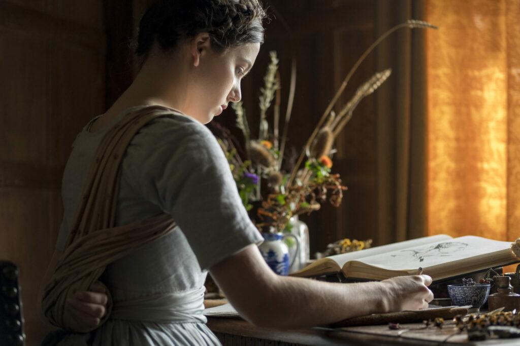 Lara befindet sich auf der linken Bildseite vor einem Tisch. Ihr linker Arm ist an den Rücken gebunden und mit der rechten Hand hält sie einen Bleistift. Vor ihr ist sichtbar ein Buch ausgebreitet. Mittig im Bild positioniert stehen Blumen und Gräser in einer Vase.