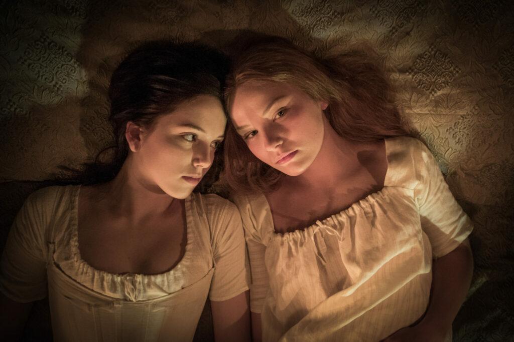 Lara und Carmilla liegen im Bett. Lara auf der linken Seite des Bildes blickt zu Carmilla auf der rechten Bildhälfte Carmilla blickt in Richtung der Kamera