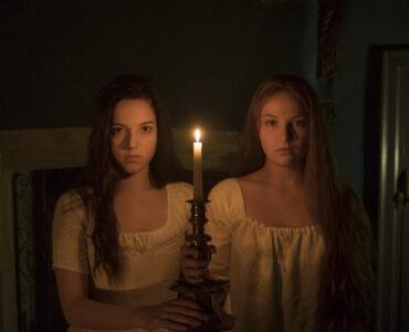 Lara auf der linken Seite des Bildes und Carmilla auf der rechten Bildseite blicken in Richtung der Kamera. Beide halten mittig positioniert einen massiven Kerzenständer, auf der eine brennende Kerze steht.