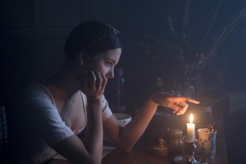 Auf der linken Bildseite ist Lara vor einem Tisch sitzend zu erkennen. Ihr rechter Arm stützt ihren Kopf, während sie den Zeigefinger ihrer linken Hand über den Schein einer Kerze hält.