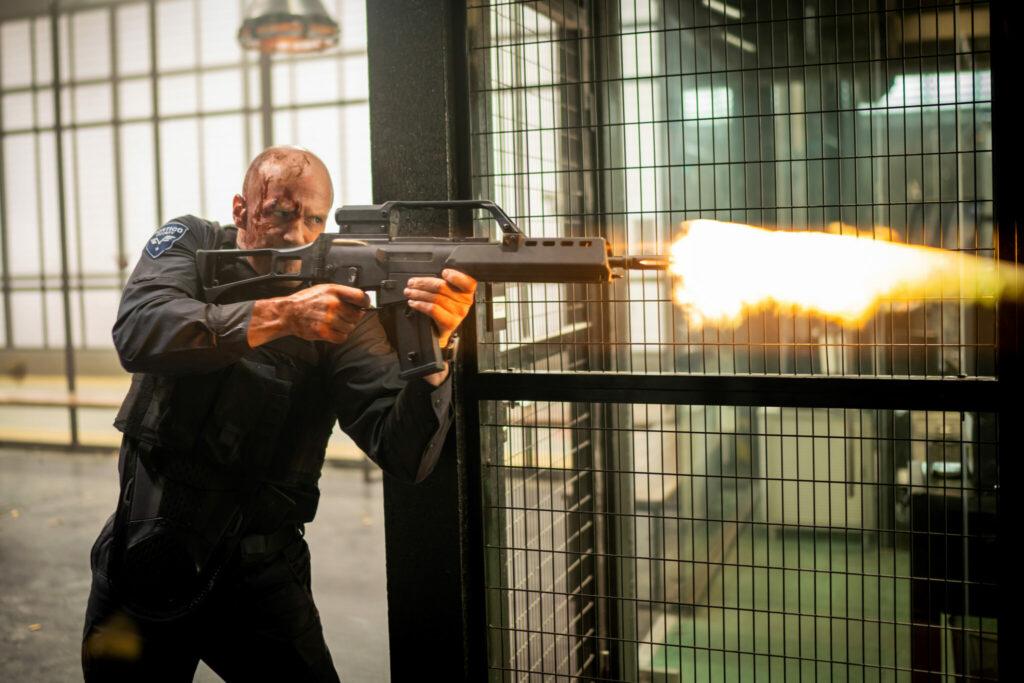 Jason Statham schaut wütend drein, Blut bedeckt sein Gesicht, und er feuert mit einem Maschinengewehr - Cash Truck