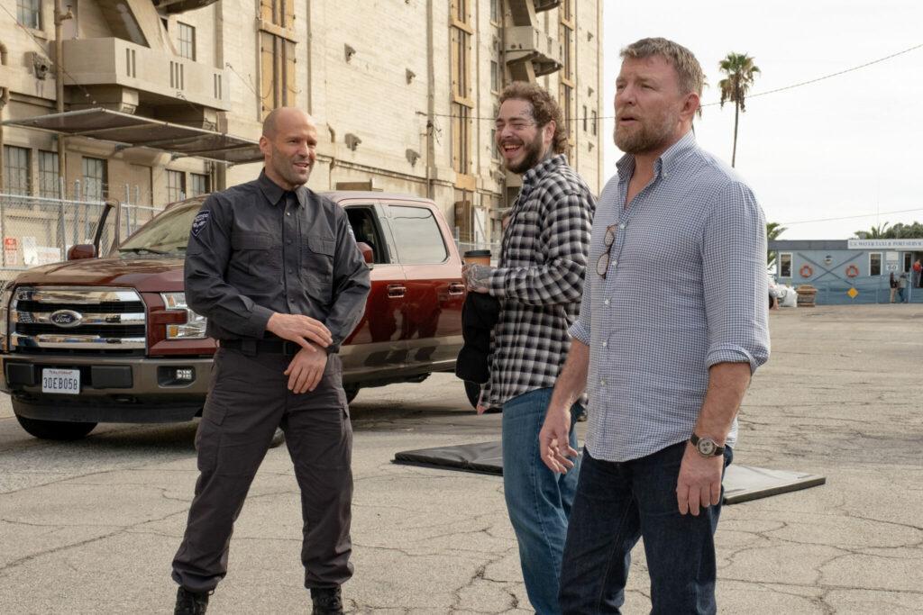 Guy Ritchie scherzt mit Jason Statham und Post Malone am Set herum, hinter ihnen steht ein SUV vor einem großen Gebäude - Cash Truck