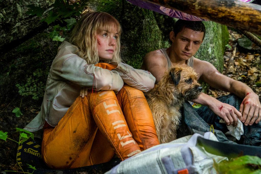 Viola Eade (Daisy Ridley) und Todd Hewitt (Tom Holland) verstecken sich im Wald und suchen während des Regens Unterschlupf unter einem Baum.