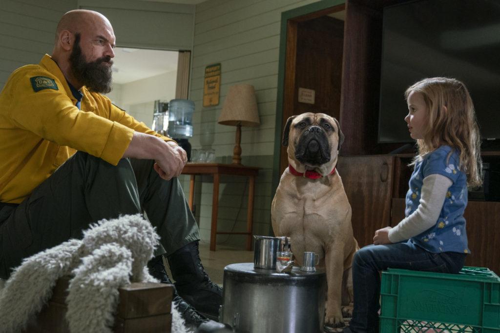 Tyler Mane & Finley Rose Slater sitzen bei einer Teestunde gemeinsam mit einem Hund. Links sitzt der riesige Mane und recht die kleine Slater. Der Hund sitzt artig zwischen den beiden in der Runde um den Tisch, auf dem ein Behälter und zwei Gläser stehen.