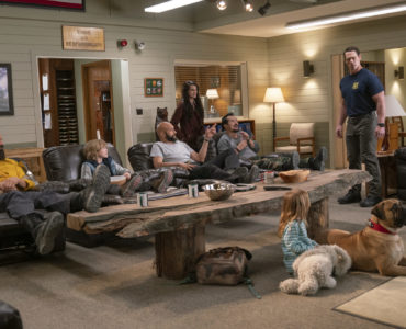 Auf diesem Bild ist der komplette Hauptcast von Chaos auf der Feuerwache zusehen. Mane, der Junge Convery, Key und Leguizamo sitzen nebeneinander auf bequemen braunen Sesseln und blicken gerade John Cena an, der zu deren linken Seite steht und sauer in Richtung des Fernsehers blickt. Zwischen den Sesseln und dem Fernseher ist ein Holztisch. Zwischen dem Tisch und dem Fernseher sitzt die kleine Slater gemeinsam mit dem Hund. Brianna Hildebrand steht zwischen den Sesseln von Key und Leguizamo und schaut ebenfalls Cena an.