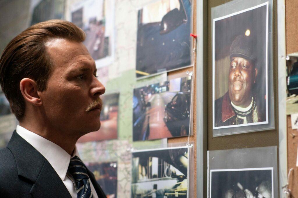 Detective Russel Poole (Johnny Depp) guckt in City of Lies auf das Portrait von Rapper Notorious B.I.G.