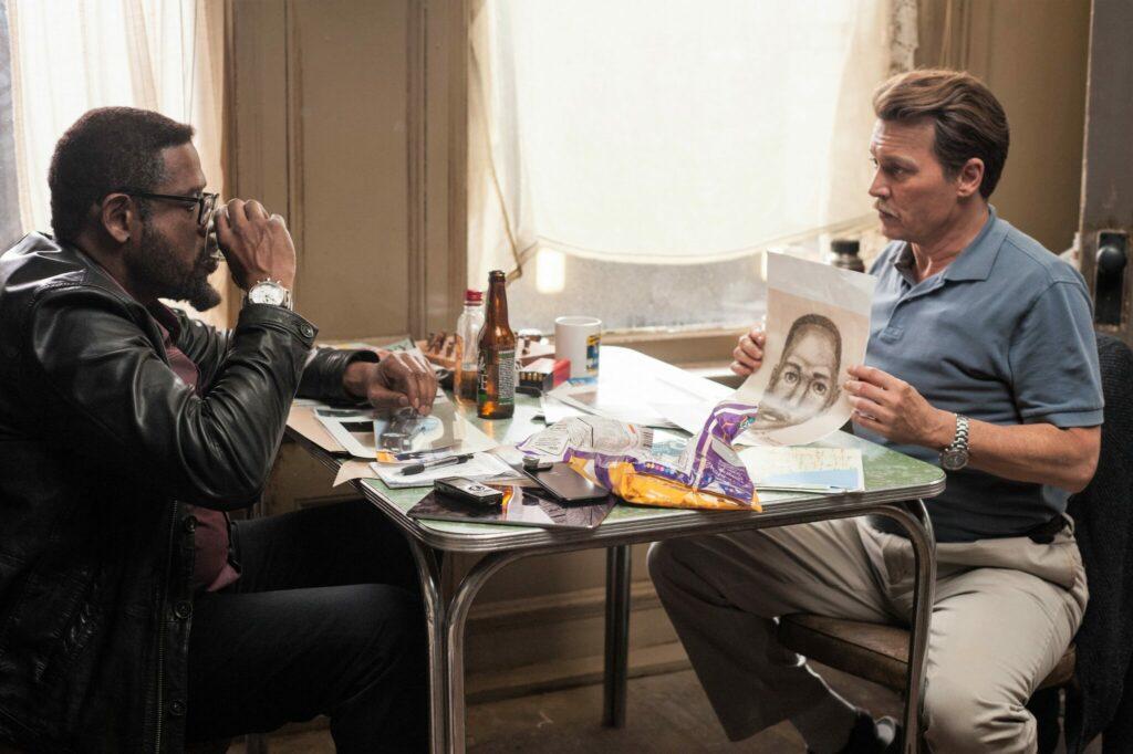 Russel Poole und Darius Jackson sitzen in City of Lies an einem Tisch. Poole weiht Jackson gerade in den Fall ein und zeigt ihm ein Phantombild.