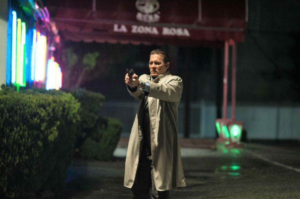 Detective Poole (Johnny Depp) im Trenchcoat, nachts, bereit zu schießen.