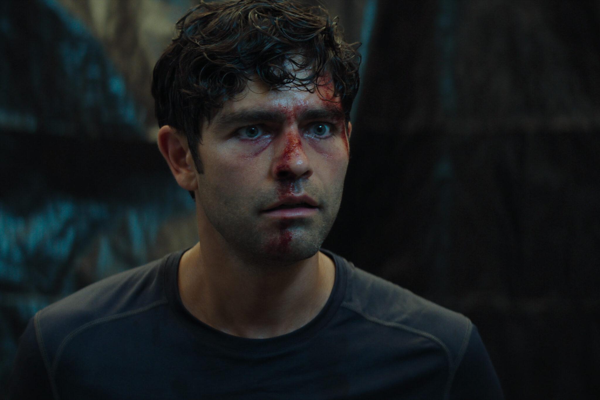 Adrian Grenier als Nick Brewer in Clickbait mit erschrockenem Gesicht und Blut auf Nase und Stirn in einem dunklen Raum.