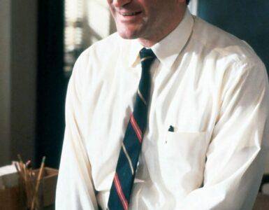 """Robin Williams als John Keating in """"Der Club der toten Dichter"""" sitzt angelehnt an seinen Tisch. Er blickt jemanden außerhalb des Bildes an und lächelt dabei. - Robin Williams Filme"""