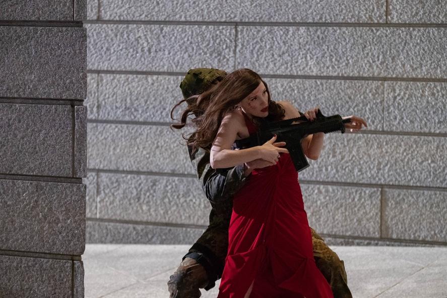 """Jessica Chastain legt sich für """"Code Ava - Trained to Kill"""" ordentlich ins Zeug. Auf dem Bild kämpft sie mit Soldaten im roten Abendkleid. Dabei überwältigt sie gerade einen Soldaten, dessen Waffe sie direkt nutzt, um auf weitere Ziele zu schießen."""