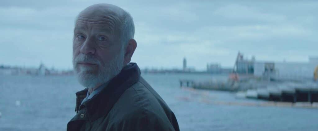 """John Malkovich spielt in """"Code Ava - Trained to Kill"""" Duke, den Mentor der Killerin Ava. Malkovich trägt wie gewohnt einen schneeweißen Vollbart und hat nur noch einen Seiten Haare. Er dreht sich gerade und spricht mit jemanden, der außerhalb des Bildes steht. Im Hintergrund ist Wasser zu erkennen, was darauf schließen lässt, dass er sich in einem Hafen oder zumindest an einer Promenade befindet."""