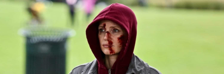 Ava (Jessica Chastain) steht an der Straße und beobachtet etwas. Sie trägt eine dunkelgrüne Jacke und einen bordeauxroten Hoodie. Die Kapuze des Hoodie ist übergezogen, verdeckt allerdings nicht die vielen Wunden in Avas Gesicht.