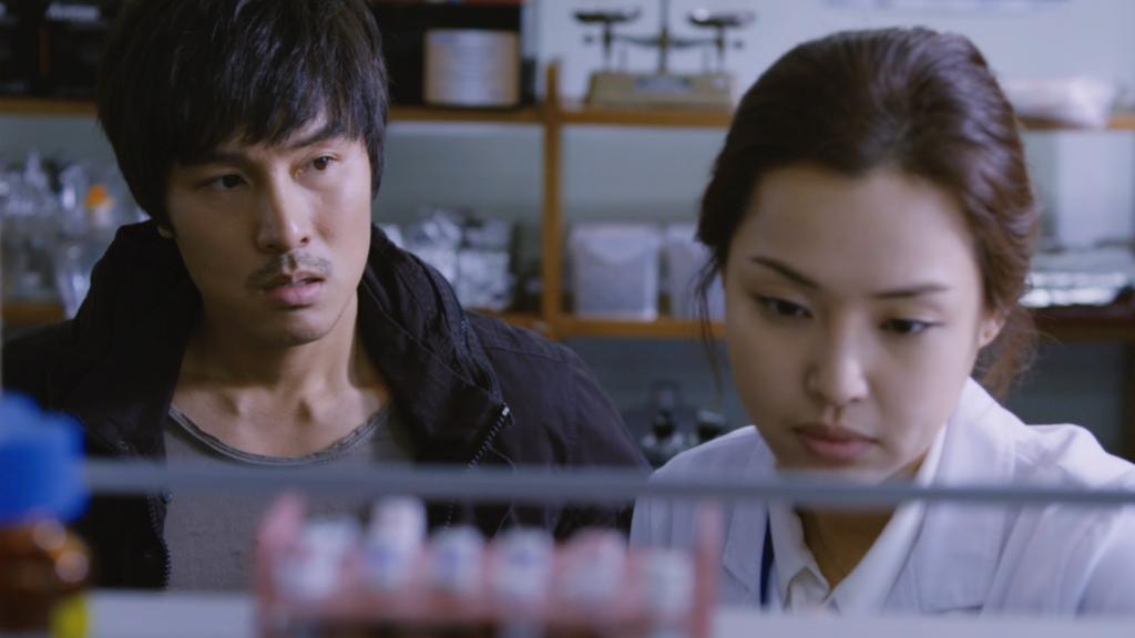 Jae-pil, gespielt von Kim Dong-wan, steht mit einer Freundin in einem Labor.