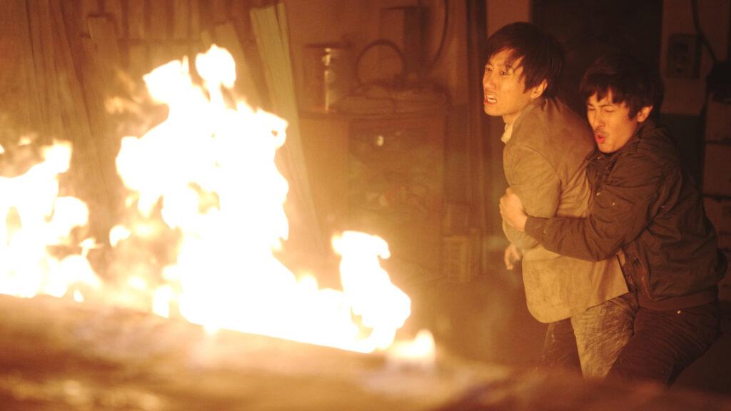 Jae-hyuk, gespielt von Kim Myeong-min, und sein Bruder Jae-pil, gespielt von Kim Dong-wan, stehen in Contamination - Tödliche Parasiten vor einer Feuerwand.