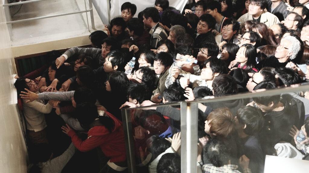 Eine Menschenmenge versucht in Contamination - Tödliche Parasiten einen Lagerraum zu stürmen.