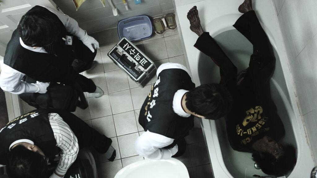 Polizisten untersuchen eine ausgezehrte Leiche, die in einer Badewanne liegt.