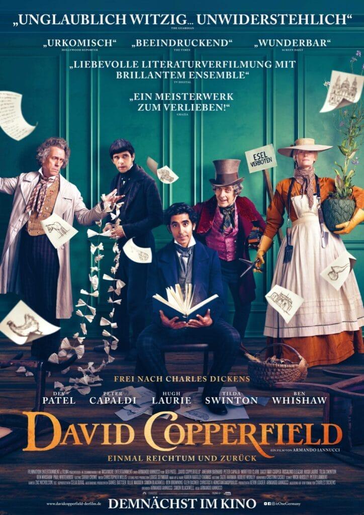 Das Filmplakat zu David Copperfield - Einmal Reichtum und zurück zeigt David Copperfield auf einem Stuhl sitzend und ein Buch in der Hand haltend, hinter ihm stehen einige Nebenfiguren vor einer grünen Wand. Einige Seiten aus dem Buch fliegen durch das Bild.