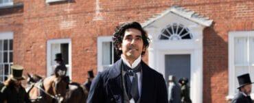 David Copperfield, gespielt von Dev Patel, steht vornehm gekleidet mit dem Zylinder in den Händen auf einer belebten Londoner Straße und blickt lachend um sich.