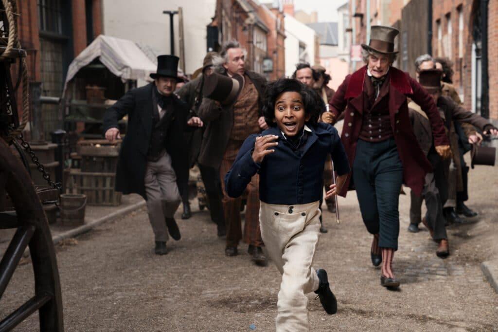 Der junge David, gespielt von Ranveer Jaiswal, flieht mit Mr. Micawber, gespielt von Peter Capaldi, vor einer Meute von Gläubigern durch eine schmale Gasse.