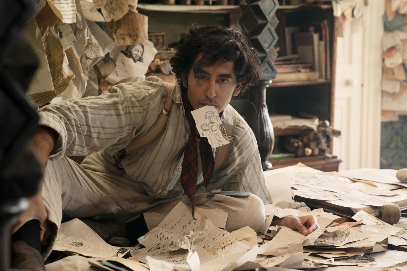 Dev Patel sitzt als David Copperfield vor einem riesigen Wirrwarr an Notizzetteln, einen dieser hält er zwischen den Lippen.