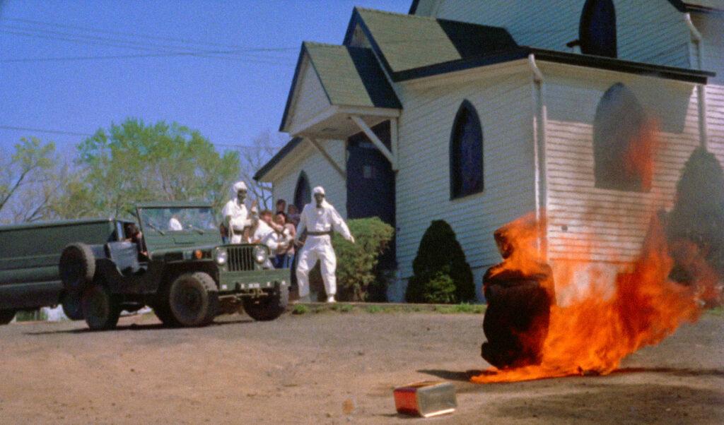 Ein Pfarrer hat sich vor einer weißen Kirche mit Benzin übergossen und angezündet. Eine Menschenmenge beobachtet ihn schockiert.