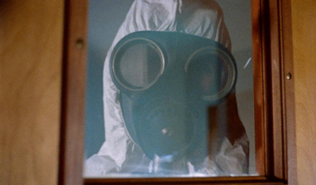 Ein Soldat in weißer ABC-Kleidung schaut in Crazies durch eine Glasscheibe.