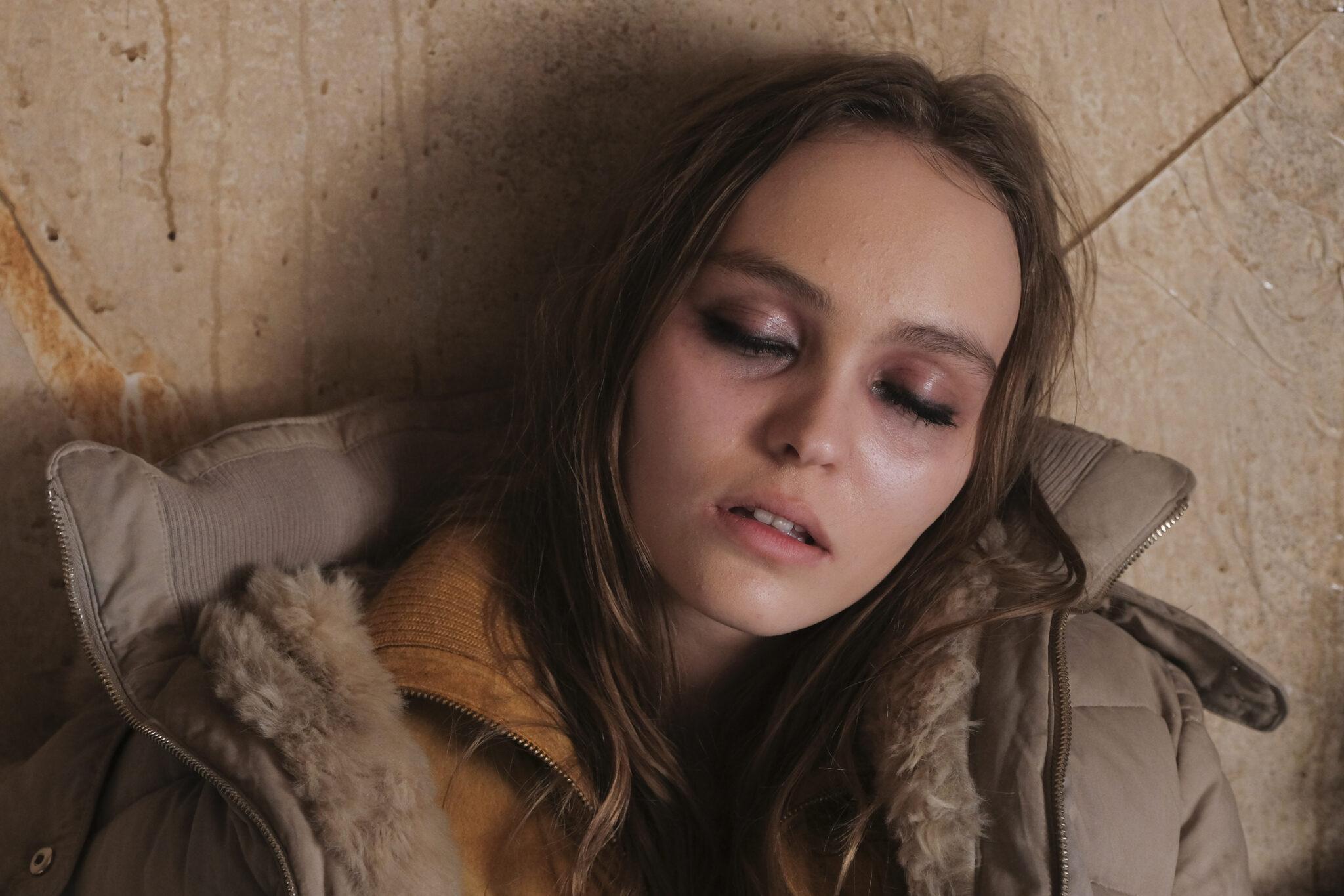 Emmie (Lily-Rose Depp) liegt bewusstlos auf dem Holzboden. Sie trägt eine gefütterte Winterjacke.