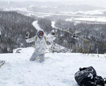 Ein Drogenkurier, ganz in weiß gekleidet, kniet auf einem schneebedeckten Hügel mit erhobenen Händen. Im Hintergrund sieht man die verschneite Wildnis und einen Helikopter herannahen. Crisis.