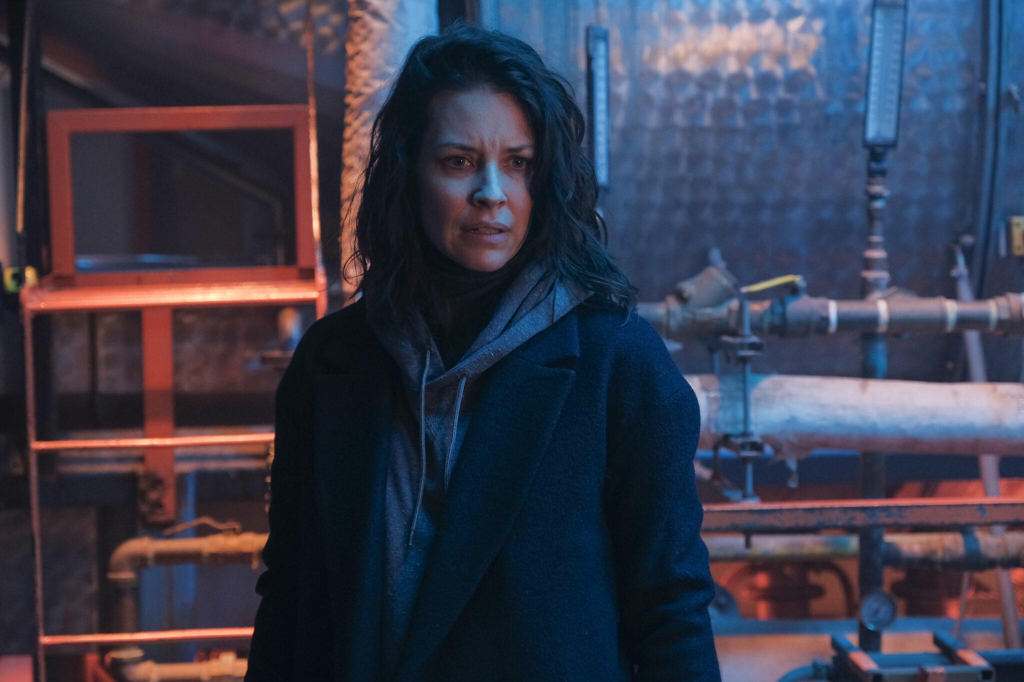 Claire (Evangeline Lilly) steht in einem Heizungskeller vor einigen Rohren und Metallwänden. Sie trägt eine schwarze Jacke über ihrem grauen Hoodie und hat dunkle, offene Haare.