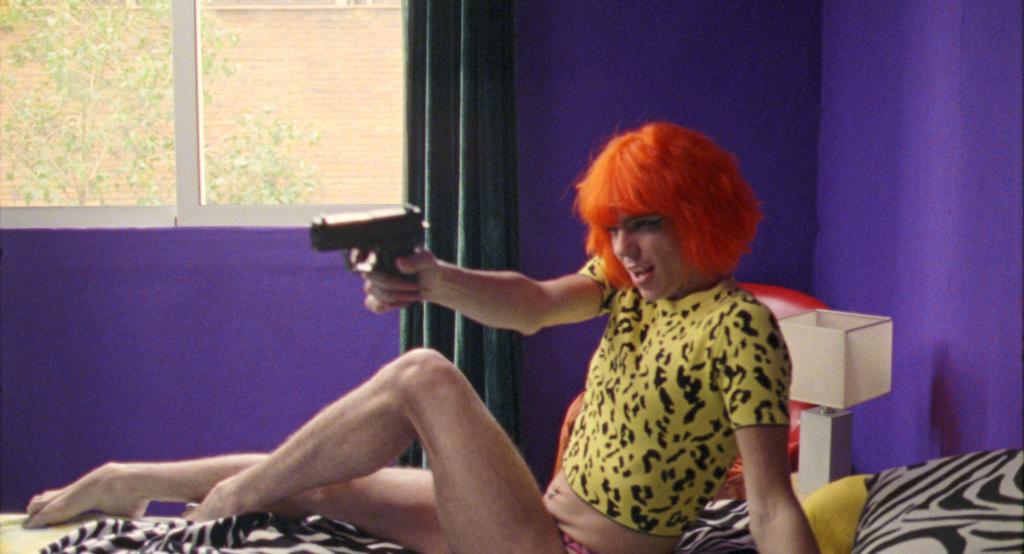 Ein Mensch in knappem Shirt und mit roter Perücke liegt auf dem Bett mit einer Pistole in der Hand