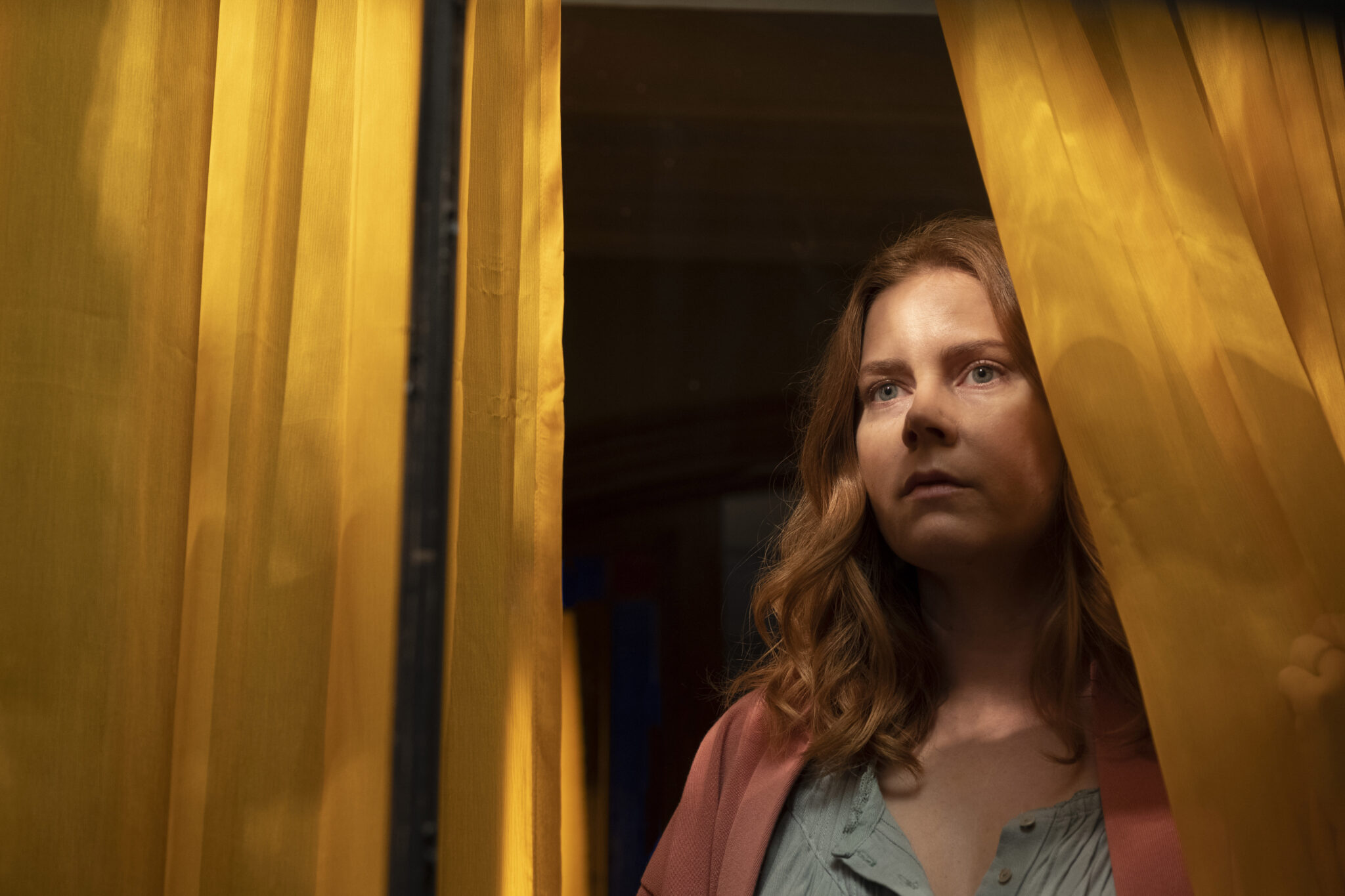 Auf dem Bild ist Amy Adams zu sehen, die zwischen zwei Vorhängen am Fenster steht und nach draußen schaut.