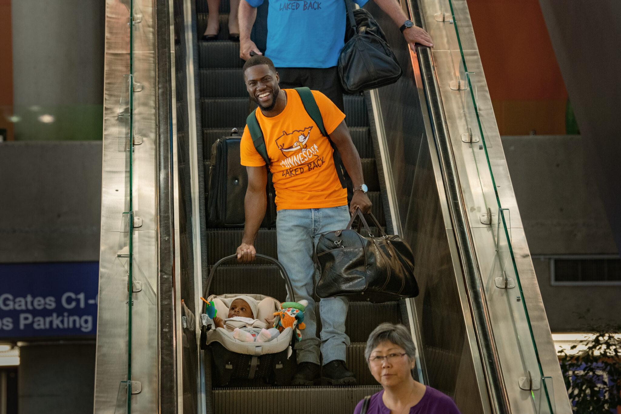Matt (Kevin Hart) auf einer Rolltreppe mit orangem T-Shirt. Er trägt in der einen Hand seine Tochter in der Wiege und in der anderen Hand eine braune Reisetasche.