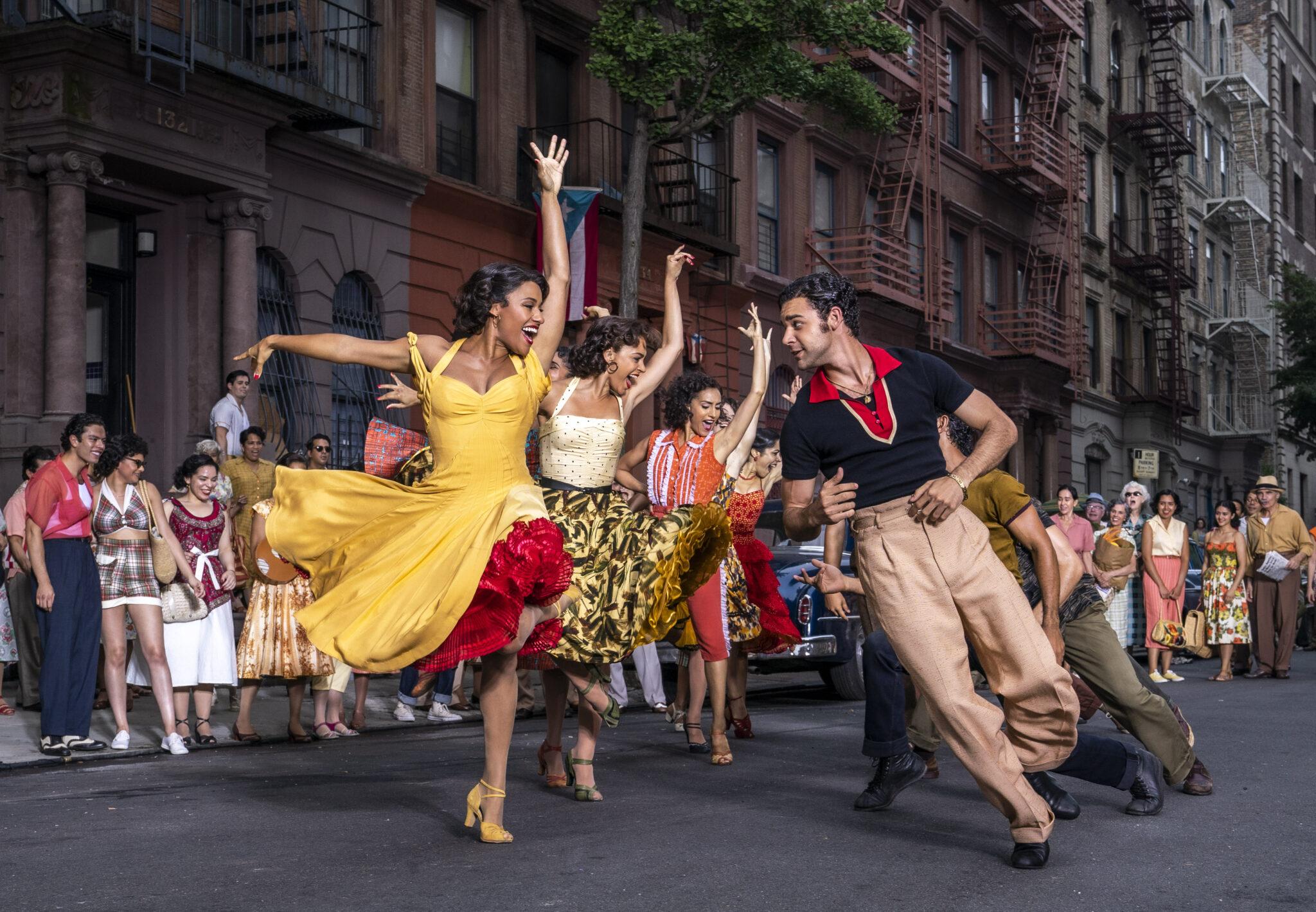 Die Szene aus West Side Story zeigt eine Tanzchoreografie auf offener Straße. Drei Frauen stehen mit erhobenen Armen drei Männern gegenüber, alle tragen bunte Kleidung. Im Hintergrund sieht man viele Zuschauer und Backsteinhäuserfronten.