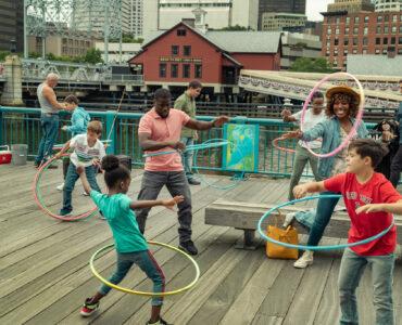 Das Bild zeigt die Hauptfiguren des Films auf einem Holzsteg mit Hula Hoop Reifen tanzend