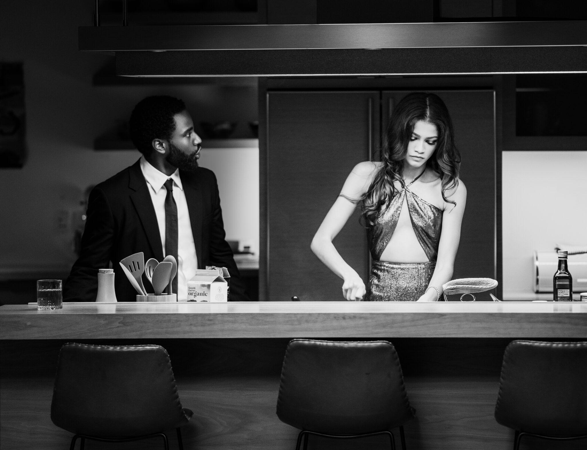 John David Washington und Zendaya hinter einer Kücheninsel. Sie schaut wütend nach unten, während sie etwas schneidet, er scheint etwas in ihre Richtung zu sagen.