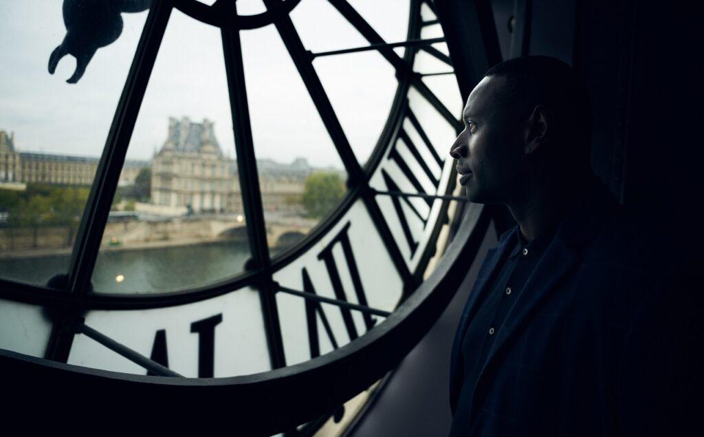 Omar Sy schaut aus seinem Versteck hinter einer Turmuhr nach Paris hinaus - Neu auf Netflix im Juni 2021